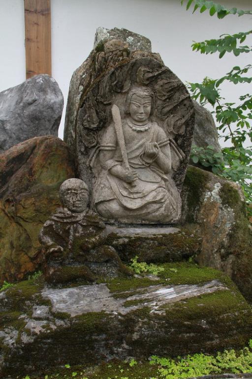 吉安慶修院-安置於手水舍後方假山的不動明王坐姿石像。拍攝:黃家榮